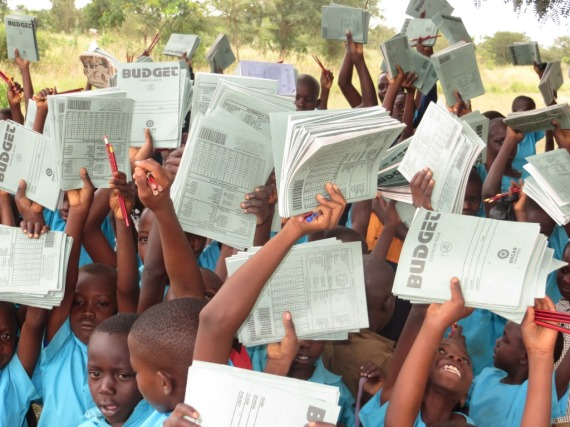 Pupils of Wesige Mukama Nursery and Primary School displaying their donated materials.